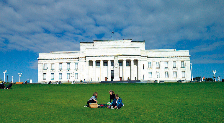 Auckland War Memorial Museum, a large white building, on an expanse of grass with picnickers