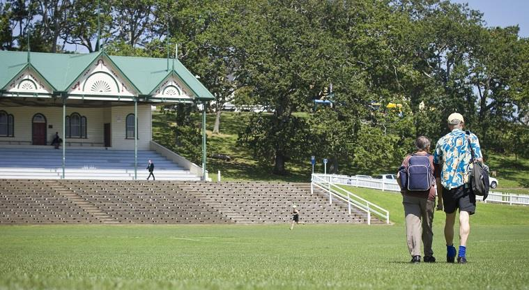 Trees, pavilion and grandstand seating sloping down to field.