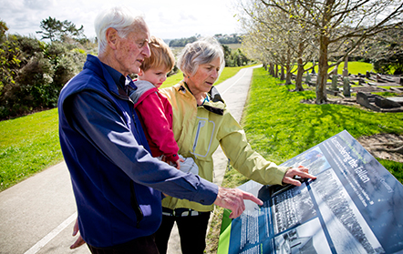 An elderly couple with a young child looking at a trail information board
