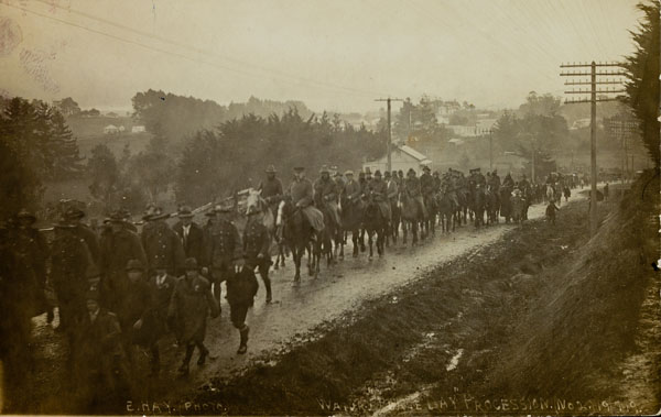 Returned soldiers parade through Waiuku on foot and horseback in heavy rain, July 1919