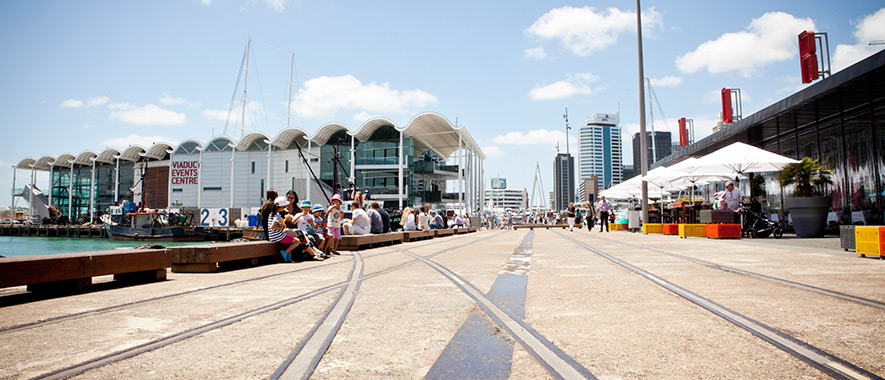 People sitting and walking on Auckland Waterfront on sunny day