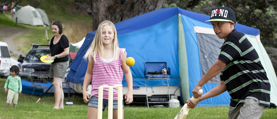 Children playing cricket at a campground.