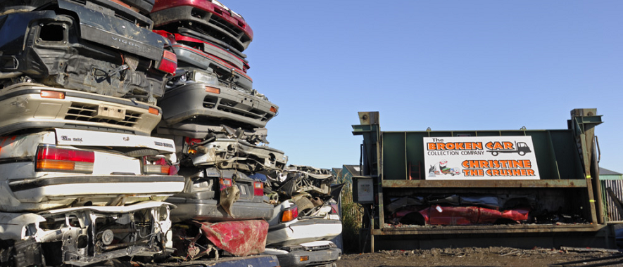 Piles of crushed cars next to a car crushing machine.