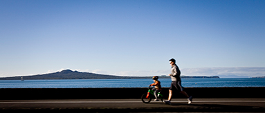 Photo of a man running and a small child on a bike along Tamaki Drive.