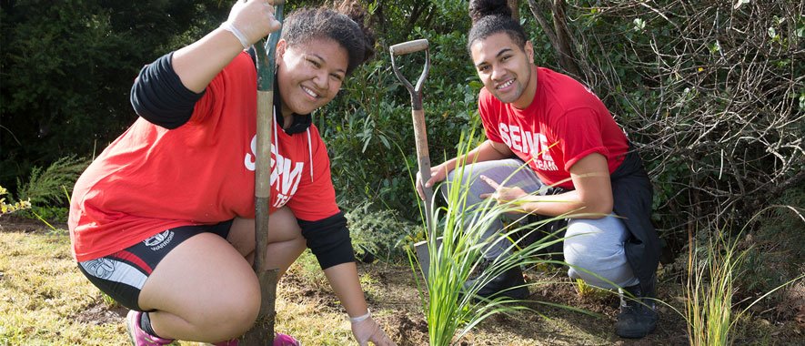 Photograph of two people at the Otara Creek planting native grass.