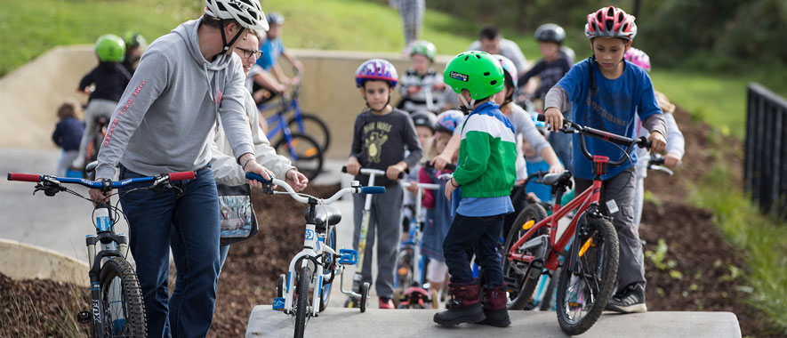 Lots of children riding their bicycles over the humps in the track at the opening of the Grey Lynn Pump Track