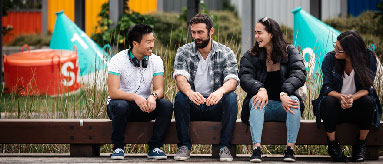 Photograph of four people sitting on bench chatting