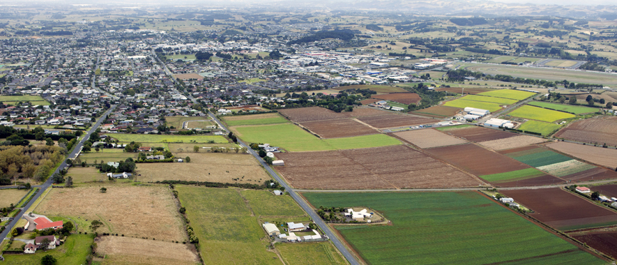 Photograph of Pukekohe from the air that shows some of the rural land and homes around the high density residential areas and town